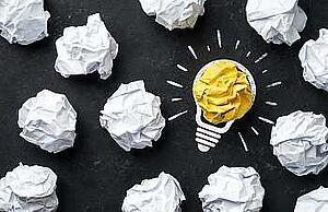 Zusammengeknüllte Papiere in weiß, in der Mitte ein gelbes, drumherum ist eine Glühbirne gemalt