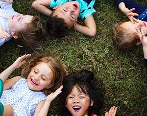 Kinder liegen im Kreis im Gras