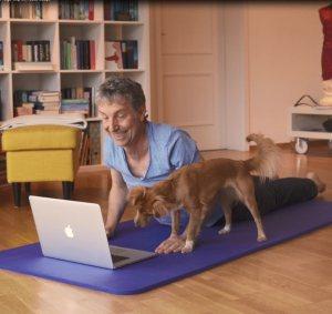 Mann und Hund machen Online-Yoga